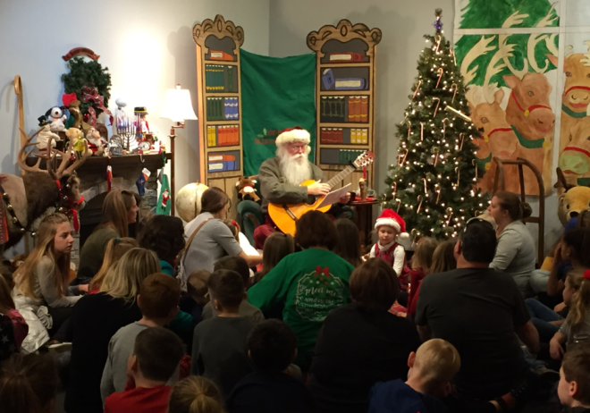 Santa playing a guitar for children in Fantasyland at the History Museum of Western Virginia