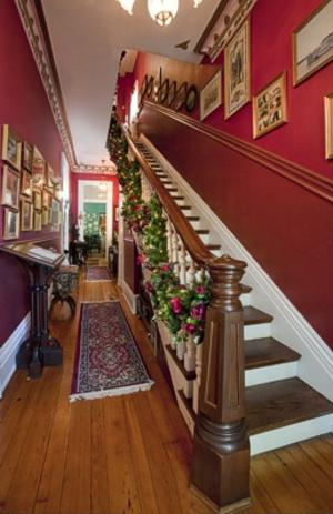 Beautiful 19th century staircase with hardwood floors and Christmas decorations and a red wall.