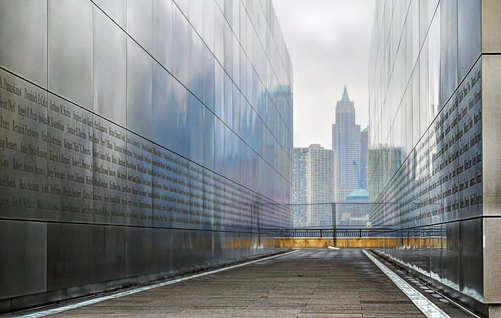 This is an image of the 9/11 memorial at Liberty State Park. The images shows two large walls forming a tunnel towards New York City. On the inside of the walls there are words of dedication to people lost at 9/11.