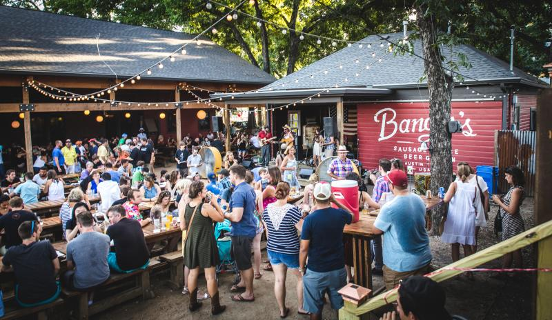 People gathering on patio at Bangers Sausage House and Beer Garden on Rainey Street in Austin Texas