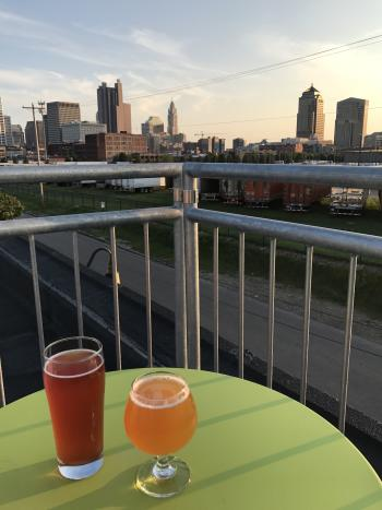 Beers on table next to railing of rooftop patio overlooking skyline at Platform Brewing