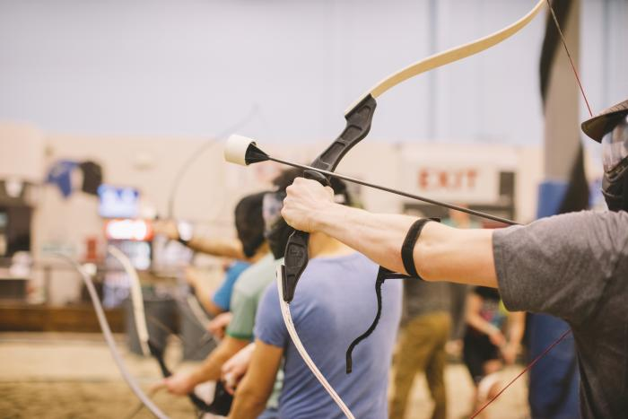 A row of people take aim with bows and foam-tipped arrows at 6Pack Indoor Beach in Richmond, BC