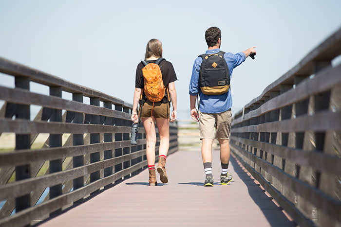 Couple walking on bridge at Bolsa Chica