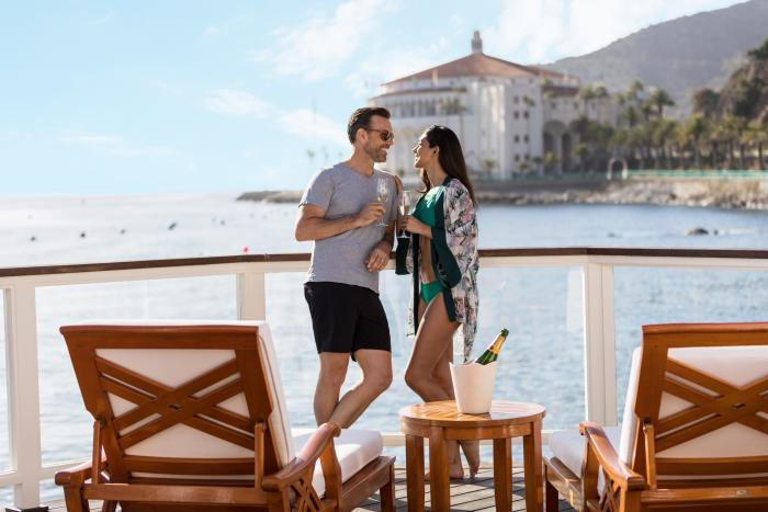 Couple on a cabana deck with chaise lounges overlooking the ocean at Descanso Beach Club on Catalina Island