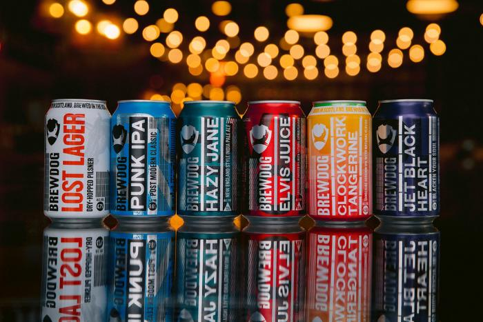 Array of BrewDog canned beer under string lights on bartop
