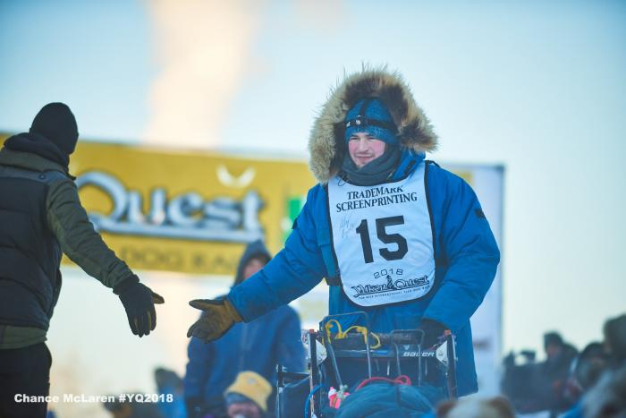 A musher shaking hands with a handler at start of race in Fairbanks
