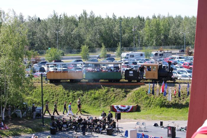 Small passenger train at a community park with crowd in foreground