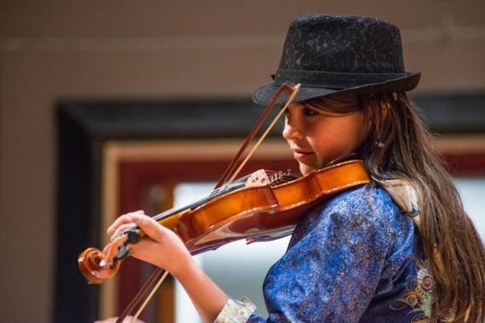 a young Alaska native woman playing a violin