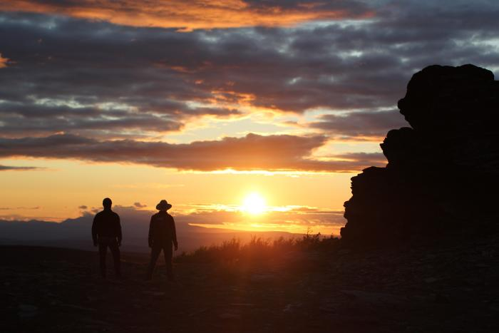 Two men watching sunset on the horizon with boulders in foreground in