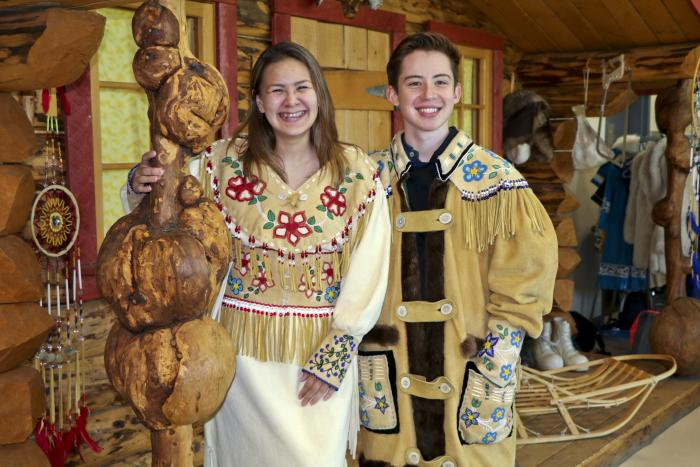 Alaska Native boy and girl dressed in traditional clothing standing next to a log cabin