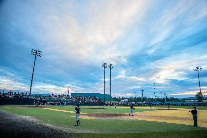 Baseball park with players on field during midnight sun season