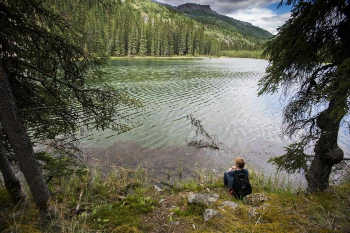 hiker sitting by a clear mountain lake