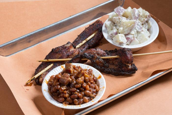 Monk's bacon on a stick with a side of baked beans and potato salad