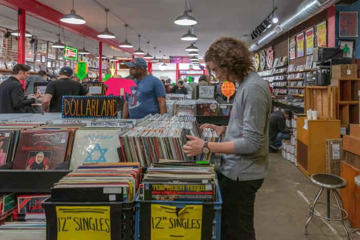 Man shuffling through crates of records at Used Kids Records