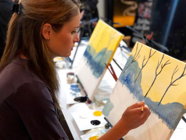 Woman in painting class working on canvas
