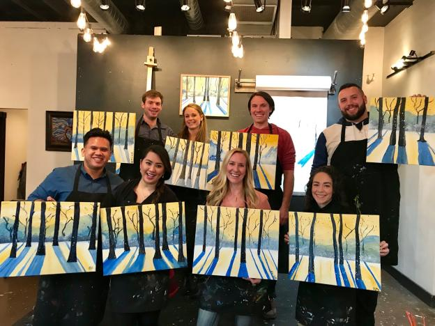 Group of adults holding finished painting after paint mixer class
