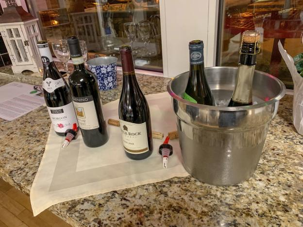 Three wine bottles of a wine selection on the counter and two in an ice bucket