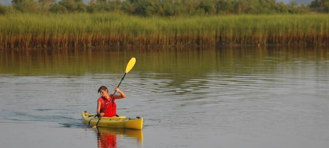 Woman in red vest kayaking in Carolina Beach salt marsh