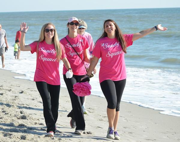 Making Strides Against Breast Cancer 5k - 3 ladies in pink t shirts walking on the beach