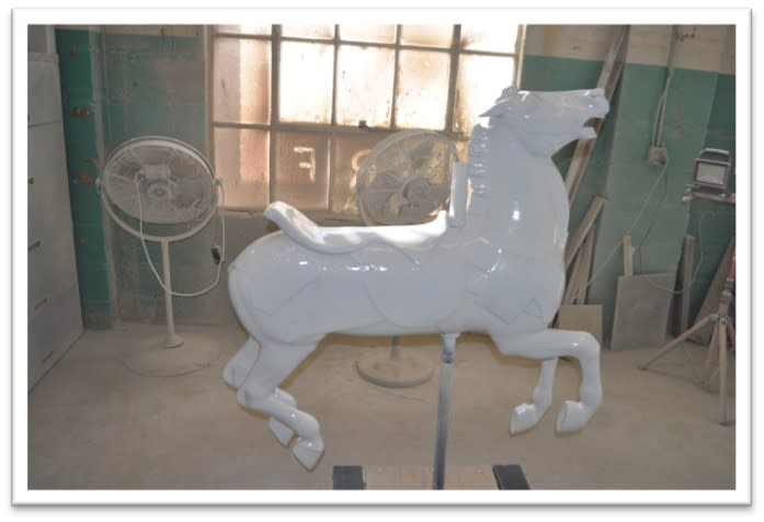 Carousel horse standing up in workshop with new coat of white finish