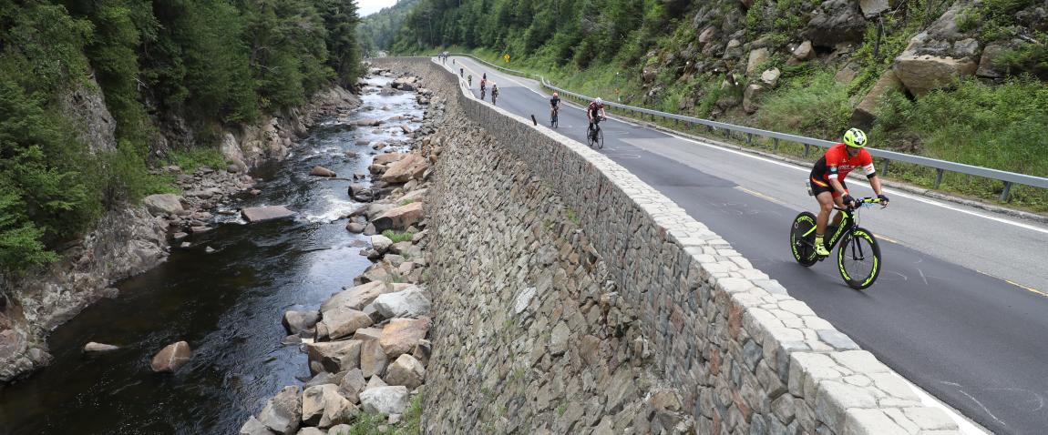 Bicyclists riding along a stream in the Lake Placid Ironman