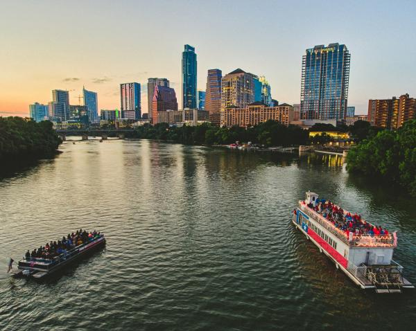 Two tour boats on Lady Bird Lake at sunset