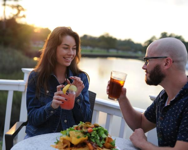 A couple holding drinks and enjoying Chesapeake food outdoors