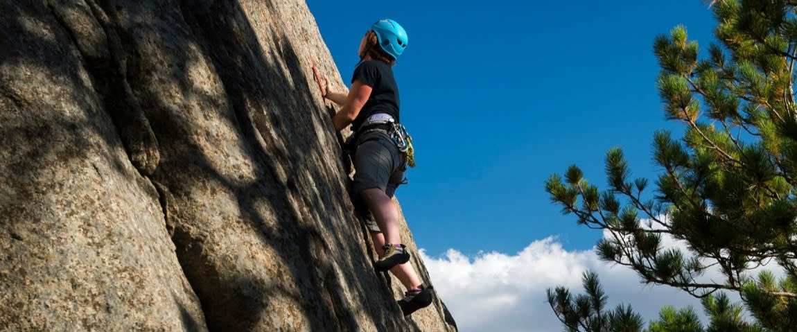 A rock climber scales a rock in the Adirondacks