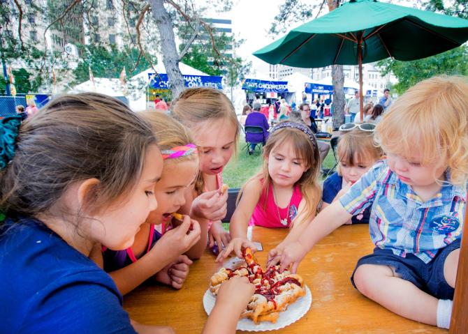 A group of kids share a funnel cake during Wichita River Festival