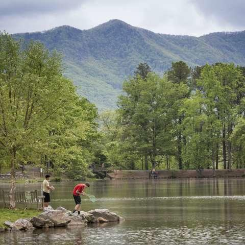 two people fishing on a rock