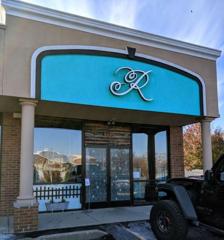 exterior photo of Repertoire restaurant in Florence Kentucky with teal wall and large cursive R on the sign