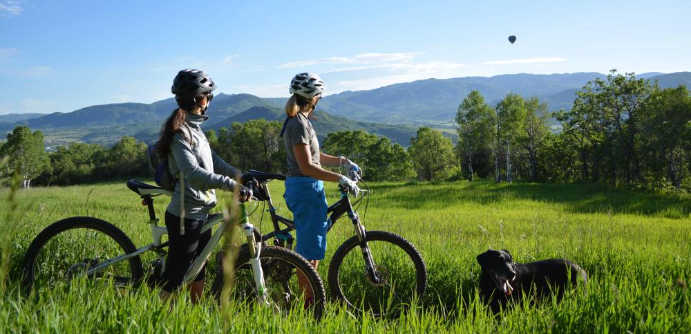 A couple enjoys the views from their bikes on Emerald Mountain