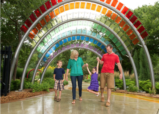 A family holds hands and walks on the rainbow trail at the Downing Children's Garden at Botanica in Wichita