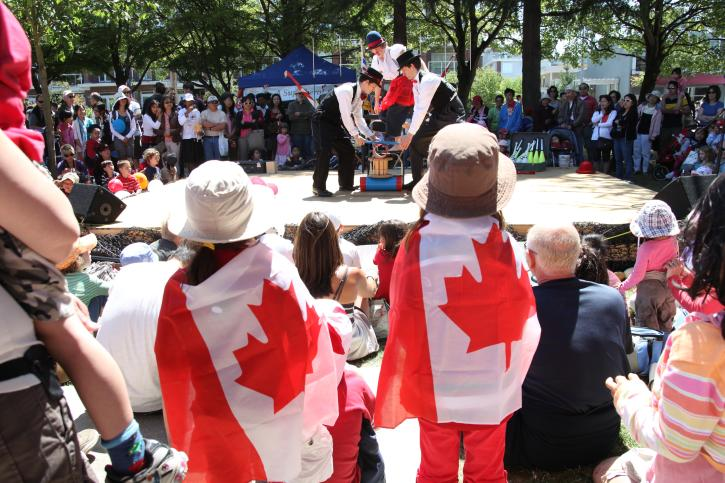 Kids wrapped in Canada flags watch a performer.