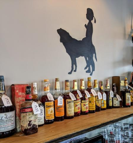 vintage bourbon selection at libbys southern comfort in covington ky including several bottles of bourbon on a shelf with a logo silhouette of a dog and little girl on the wall