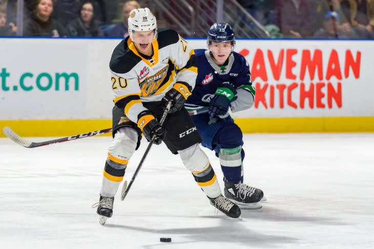 A Brandon Wheat Kings player chases the puck as a player from the opposing team follows close behind