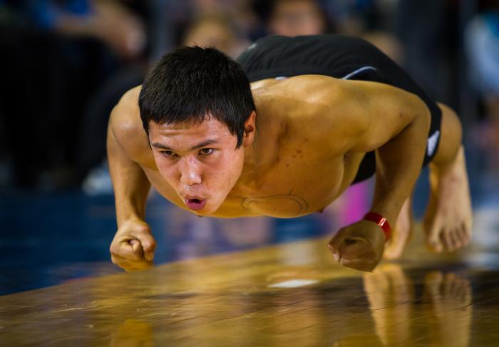 athletic young man hopping across a wooden floor on knuckles and toes