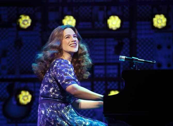 Carole King smiles while playing the piano