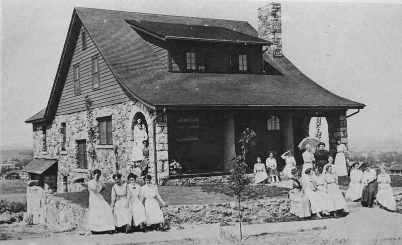 Black and white photo of Bluebird Cottage with several women sitting out front