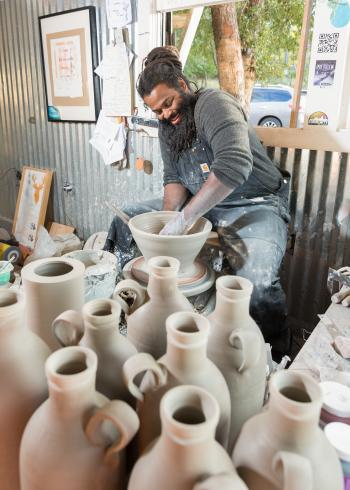 Man working at wheel in studio surrounded by clay jars at Ro Shaw clay studio in salado texas