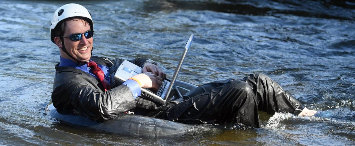Man wearing a white helmet in a suit holding a laptop floating down the river