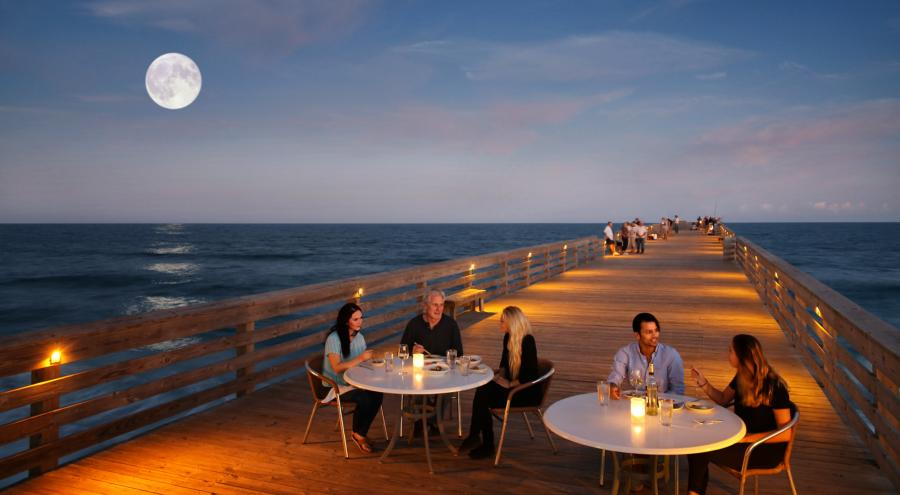 People dining at tables on a boardwalk on the ocean with a full moon behind them