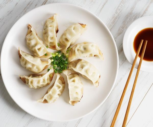 A plate of gyoza sit on a plate, served with dipping sauce and sliced green onion.