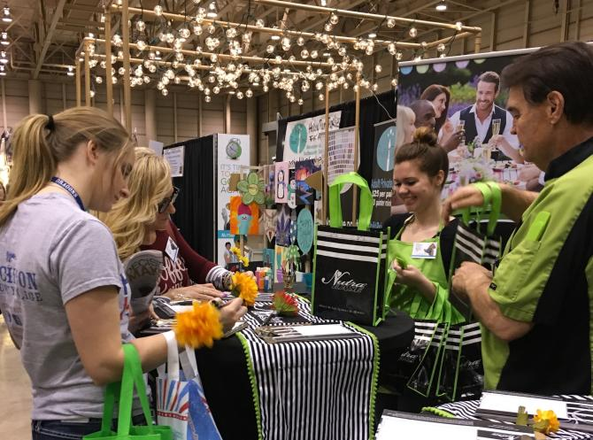 A group of women visit a booth at the Wichita Women's Fair at Century II