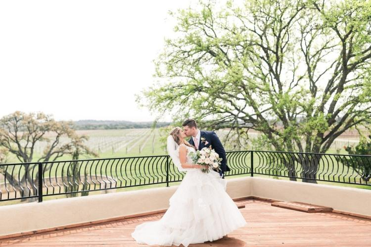 Bride and groom kissing with a view of the Texas Hill Country behind them