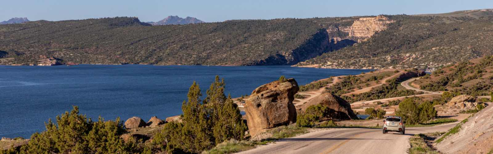 A car is driving along a windy road with the Alcova Reservoir lake on the left.