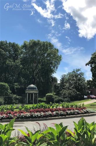 Entrance to Congress Park lined with beds of green plants and red and white flowers.