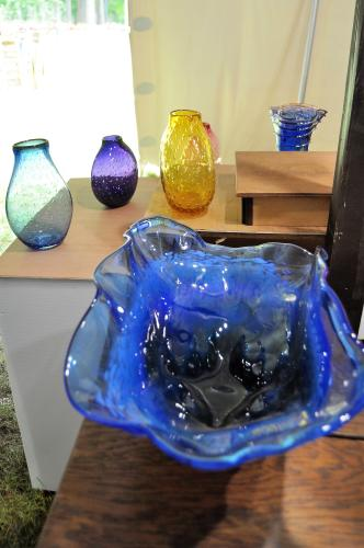 Pieces of glass art work including a large blue bowl with three vases behind it in varying colors