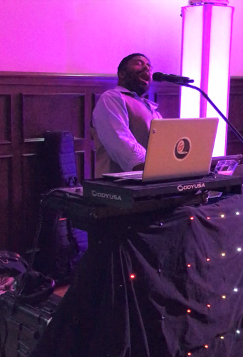 Garland Nelson singing with head thrown back and eyes shut at reception behind a table with tiny white lights and purple lighting