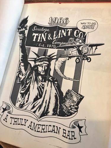 1986 pen and ink ad for Tin and Lint featuring Statue of Liberty and old plane